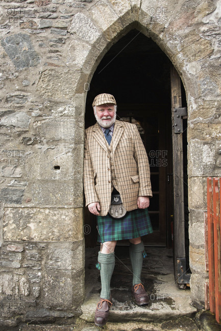 April 24, 2017: Portrait of mature man wearing traditional kilt leaning on archway of Eilean Donan Castle, Scotland, UK