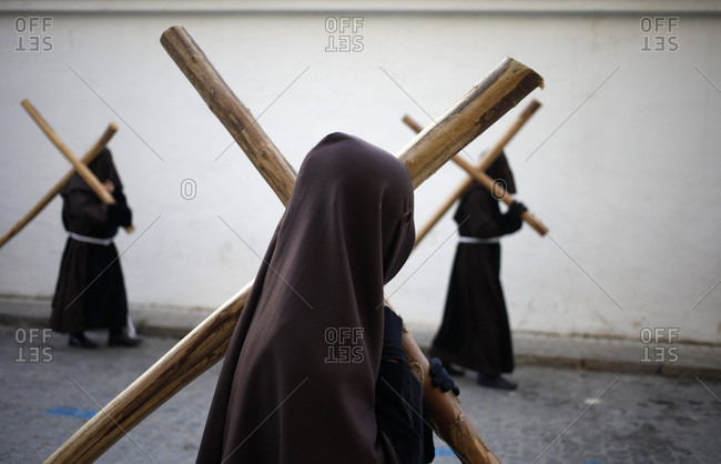 April 14, 2017: Hooded penitents carry crosses during Easter Week celebrations in Baeza, Jaen Province, Andalusia, Spain