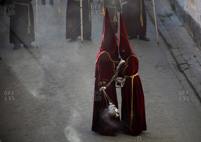 April 13, 2017: Altar servers wearing red clothing and pointed hoods talking during Easter Week celebrations in Baeza, Jaen Province, Andalusia, Spain