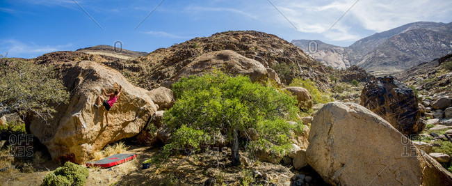 August 6, 2014: Young woman bouldering on sunny day, Brandberg, Damaraland, Namibia