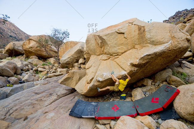 August 14, 2014: Man climbing boulder, Brandberg, Damaraland, Namibia