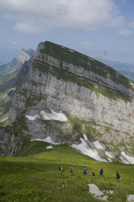 July 14, 2013: Group of friends hiking in Alps during sunny weather, Toggenburg, Switzerland