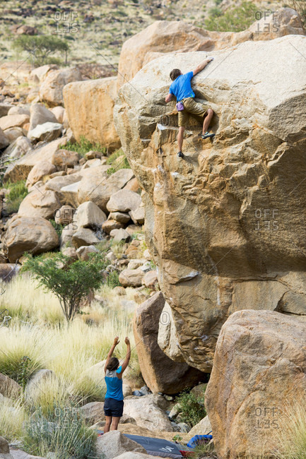 August 15, 2014: Man bouldering and woman watching from below, Brandberg, Damaraland, Namibia