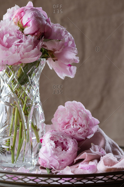 Pink peonies with pink linen on a marble table