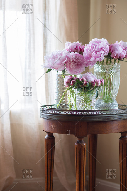 Pink peonies in glass vases on a marble table