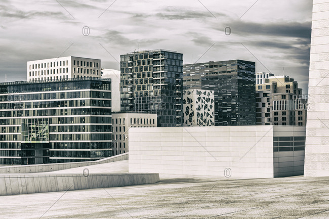 Oslo, Norway - July 18, 2013: The Oslo Opera House (Operahuset), Snohetta architects, and some new buildings of Bjorvika Barcode (masterplan designed by MVRDV of Rotterdam and the Norwegian firms DARK Architects and A-lab)