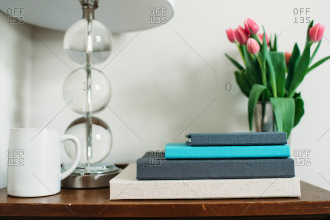 Photo albums on a table by tulips and a lamp and coffee mug