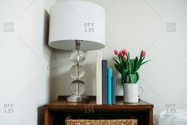 Photo albums on a table by tulips and a lamp