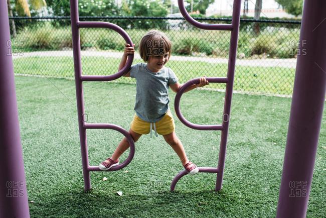 Toddler girl climbing at a playground