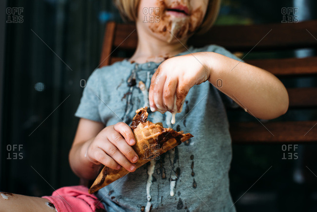 Little girl eating a really messy ice cream cone