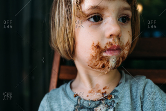 Little girl with a messy face after eating an ice cream cone