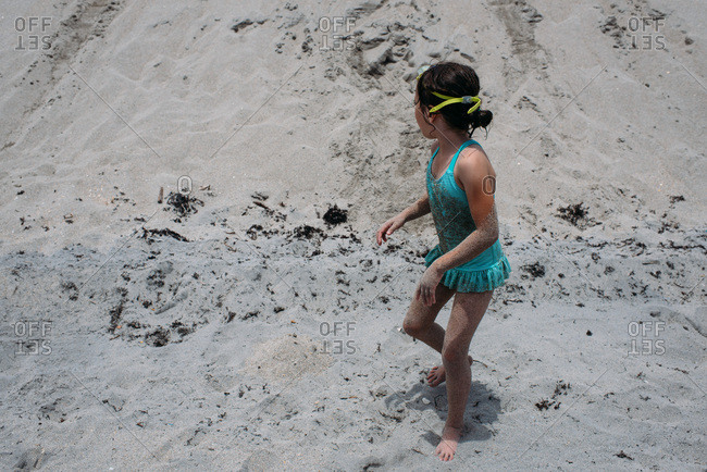 Little girl covered in sand on a beach