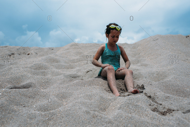 Little girl sitting in sand on a beach