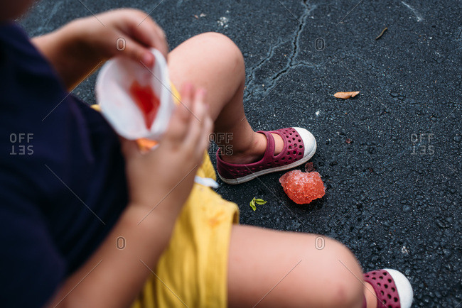 Toddler girl dropping a red snow cone on ground