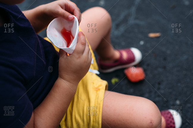 Toddler dropping a red snow cone on ground