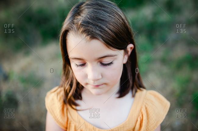 Solemn portrait of little brunette girl at dusk