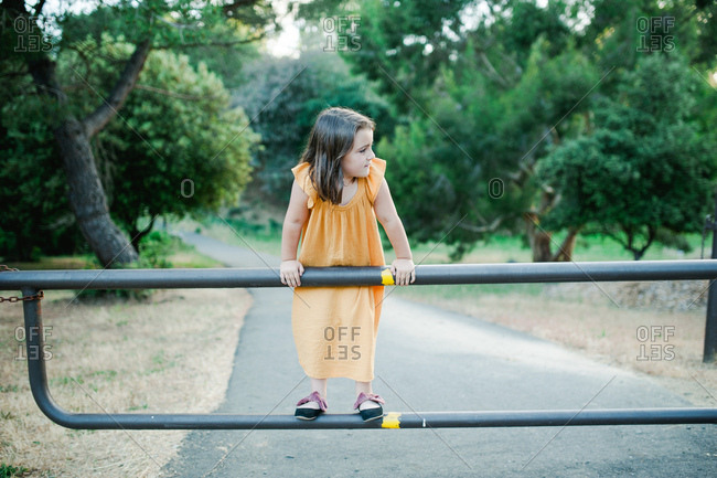 Little girl balancing on country driveway gate