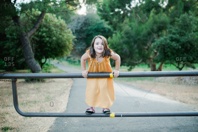 Young girl posing on metal fence in the country