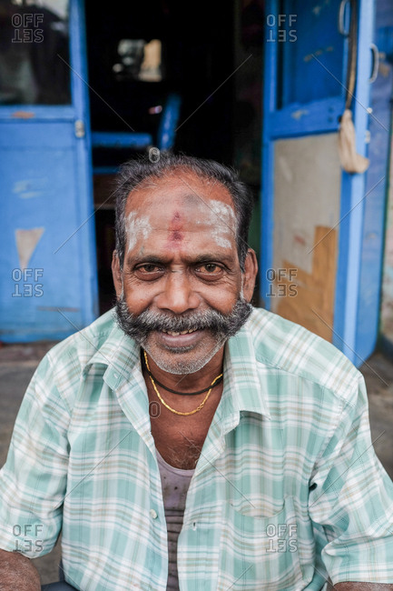 Pondicherry, India - December 7, 2016: Man sitting outside of a barbershop