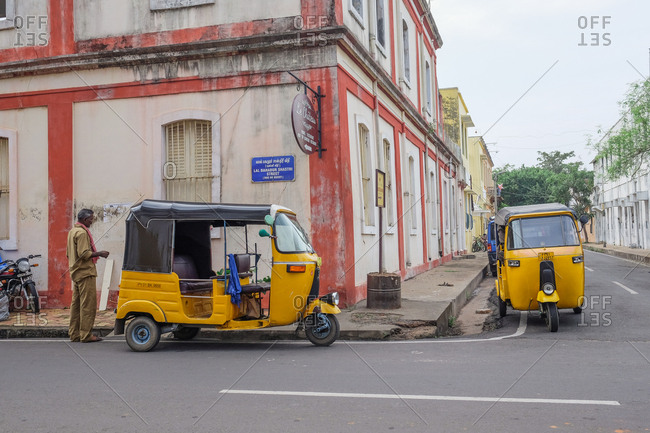 Pondicherry, India - December 7, 2016: Yellow auto rickshaws parked on city street