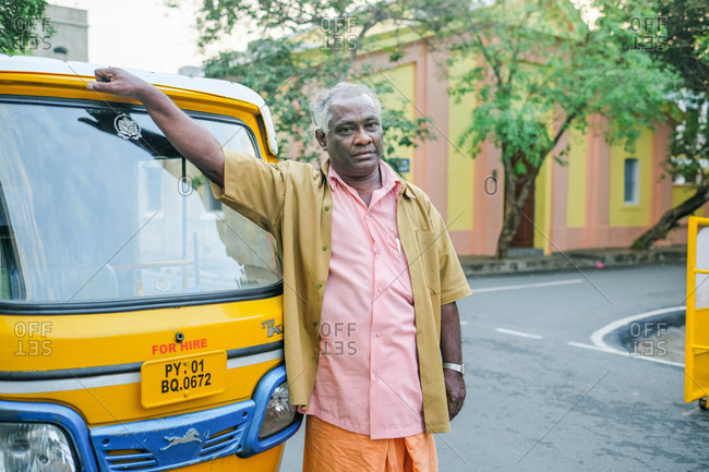 Pondicherry, India - December 7, 2016: Cab driver standing beside his auto rickshaw
