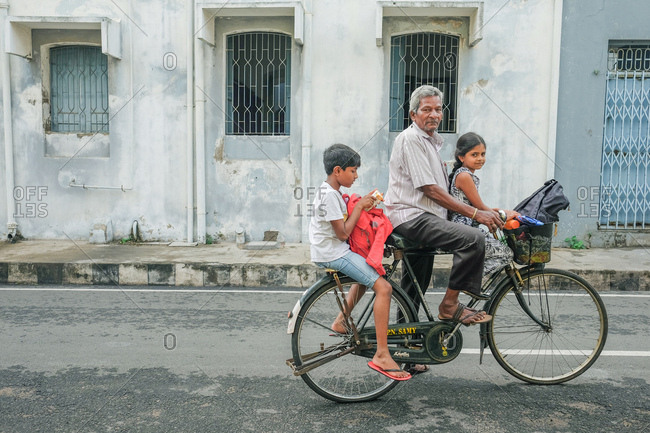 Pondicherry, India - December 7, 2016: Man riding bicycle on city street with two children