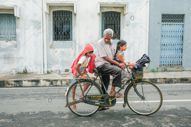 Pondicherry, India - December 7, 2016: Man riding bicycle on city street with his grandchildren