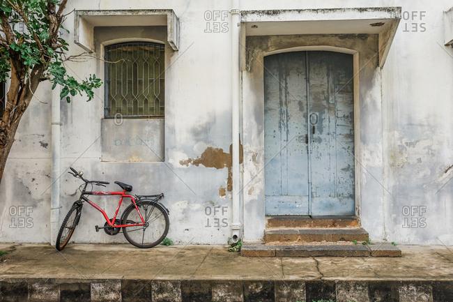 Pondicherry, India - December 7, 2016: Bike parked on sidewalk by building entrance