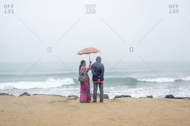 Pondicherry, India - December 7, 2016: Couple standing by ocean with umbrella