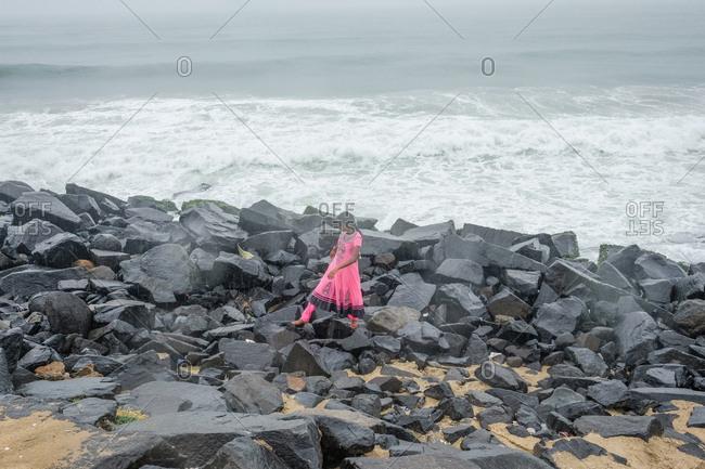 Pondicherry, India - December 7, 2016: Woman walking on rocks by ocean