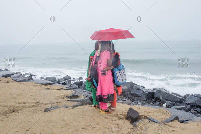 Pondicherry, India - December 7, 2016: Women standing under umbrella by the ocean
