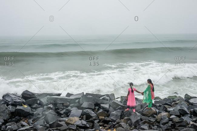 Pondicherry, India - December 7, 2016:  Two women walking hand in hand on rocks by ocean