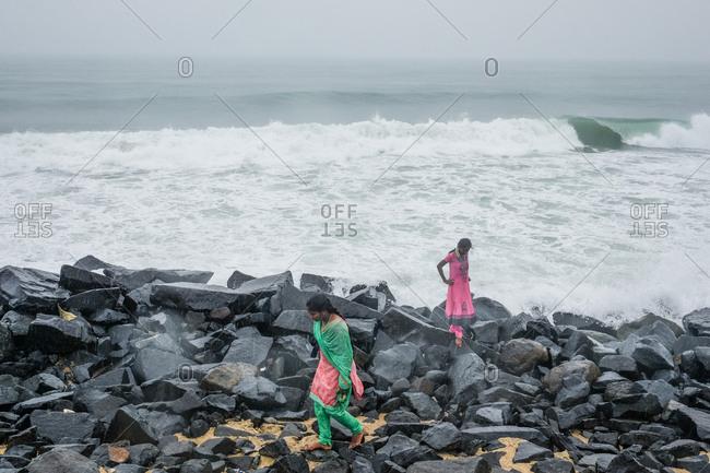 Pondicherry, India - December 7, 2016:  Two women walking on rocks by ocean