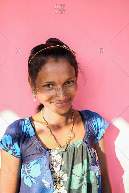 Saputara, India - November 24, 2016: Portrait of an Indian girl wearing a floral dress on pink background