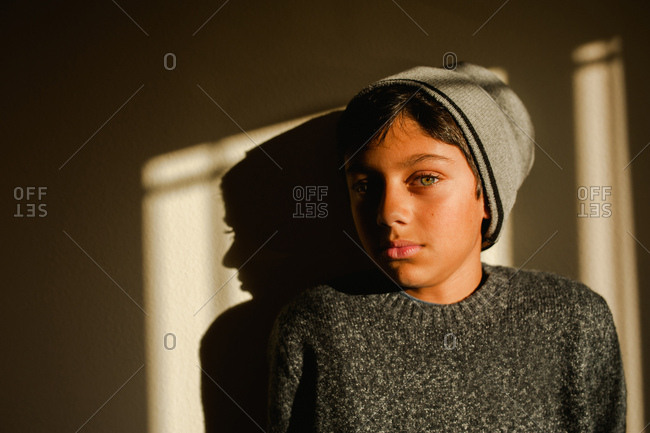 Portrait of young teen boy wearing gray sweater and knit hat