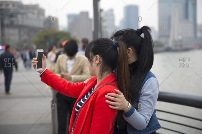 Shanghai, China - March 30, 2018: Two young women taking selfies on The Bund walking area