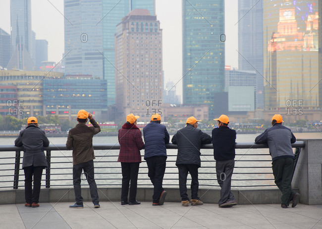 Group of tourists in matching baseball caps looking at Pudong business district