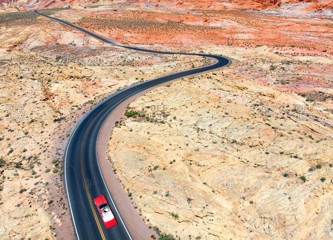 Aerial view of vintage car driving on deserted road in Fire Valley Park