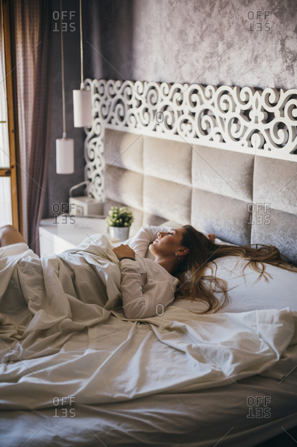 Young woman sprawled out on asleep on large bed in hotel room