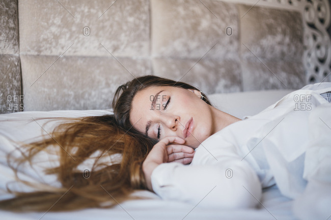 Low angle view of young woman asleep on back with head turned to side