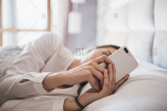 Close up of young woman's hands using smartphone while lying in bed