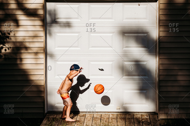 Young boy bouncing basketball outside garage on sunny afternoon