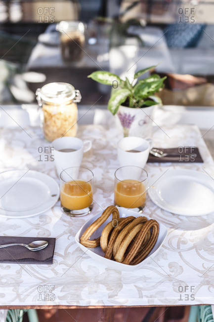Breakfast table with orange juice for two and Spanish churros