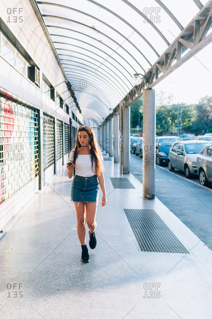Young woman using smart phone while walking