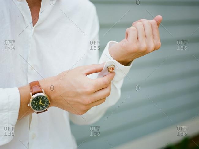 Person putting cufflinks on shirt