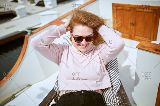 Smiling young woman relaxing on sailboat with hands behind head