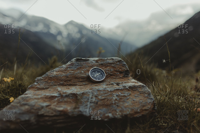 Navigational compass sitting open on rock in large wilderness