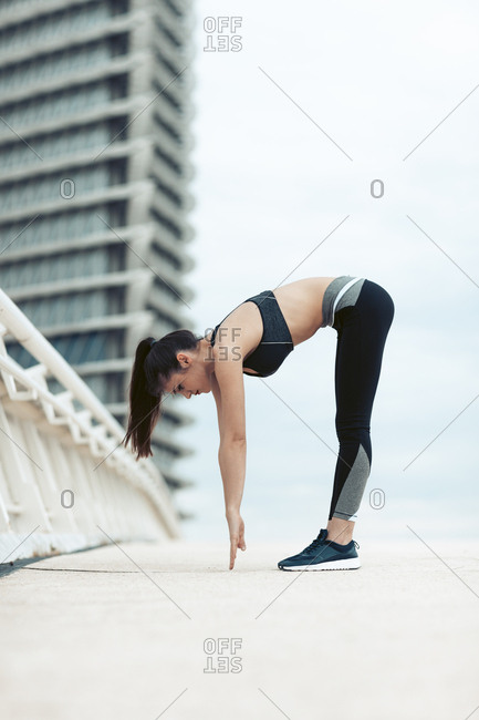 Flexible woman in sportswear bending over and touching floor while stretching