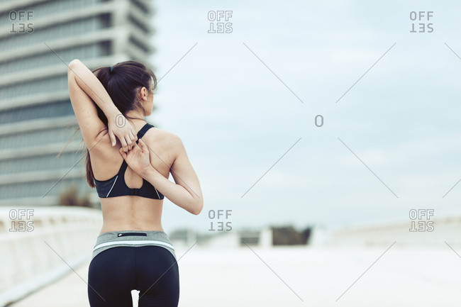 Rearview of young woman in sportswear looking to side and linking fingers behind back