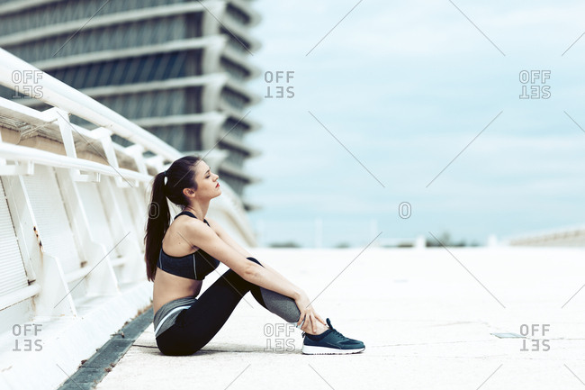 Young woman in sports wear sitting on bridge taking break during workout